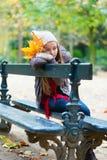 Droevige meisjeszitting op een bank in park royalty-vrije stock afbeeldingen