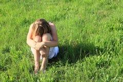 Droevige meisjeszitting op gras Royalty-vrije Stock Foto's