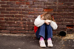 Droevige meisjeszitting tegen bakstenen muur Royalty-vrije Stock Fotografie