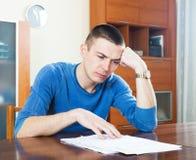 Droevige mens die financieel document in frustratie bekijken Royalty-vrije Stock Fotografie