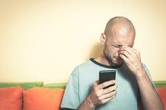 Droevige mens die zijn celtelefoon in zijn handen en schreeuw houden omdat zijn meisje met hem over het tekstbericht verdeelt stock afbeeldingen