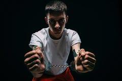 Droevige mens in gevangenis eenvormige tonende manchetten stock afbeelding