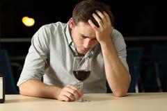 Droevige mens het drinken wijn in een bar Stock Afbeeldingen