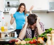 Droevige mens met boze vrouw bij keuken Royalty-vrije Stock Afbeeldingen