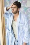 Droevige mens met thermometer in mond die bij deuropening gereed staat Royalty-vrije Stock Foto's