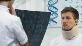 Droevige mens in schuim cervicale kraag op artsenbenoeming, negatief x-ray resultaat stock video