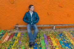 Droevige mensenzitting op een bank onder gevallen bladeren Stock Foto's