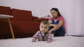 Droevige moeder die met wapens rond knieën op baby letten stock video
