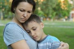 Droevige moeder met zoon in park royalty-vrije stock afbeelding
