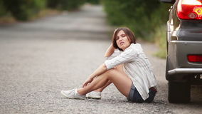 Droevige mooie meisjeszitting op de weg na autoongeval stock videobeelden