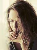 Droevige mooie vrouw die met lange krullende haren neer kijken Stock Afbeeldingen