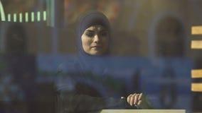 Droevige Moslimdame die in traditionele hijab in koffie over huis, emigratie denken stock video