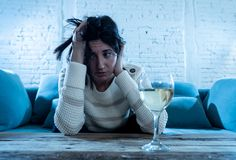 Droevige, ongelukkige, hulpeloze vrouw het drinken wijn alleen thuis Menselijk emoties, depressie en alcoholisme royalty-vrije stock foto