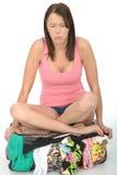 Droevige Ongelukkige Jonge Gekruist Vrouwenzitting Legged op een Overlopende Koffer royalty-vrije stock foto