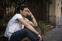 Droevige, ongelukkige jonge mens openlucht, zittend op bestrating Royalty-vrije Stock Afbeeldingen