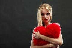 Droevige ongelukkige vrouw die rood harthoofdkussen houden Royalty-vrije Stock Afbeeldingen