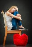 Droevige ongelukkige vrouw met rood harthoofdkussen Stock Foto's