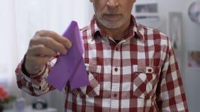 Droevige oude mens die purper lint, kanker en Alzheimers-ziektevoorlichting houden stock footage