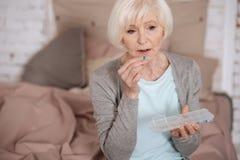 Droevige oude vrouw die pil nemen stock afbeelding