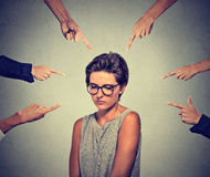 Droevige pijnlijke vrouw die in glazen onderaan vele vingers die haar bekijken richten Stock Fotografie