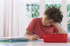 Droevige schooljongen die thuiswerk doet royalty-vrije stock afbeeldingen