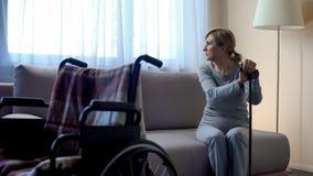 Droevige teruggetrokken dame die op echtgenoot bij ziekenhuis wachten, die in venster het kijken, rehab stock afbeelding