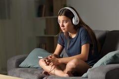 Droevige tiener die aan alleen muziek thuis luisteren stock fotografie