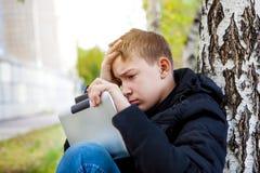 Droevige Tiener met Tabletcomputer Stock Afbeeldingen