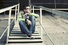 Droevige tienerjongen in depressiezitting op de stappen Stock Afbeeldingen