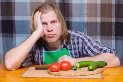 Droevige vermoeide mens met tomaten en komkommers Royalty-vrije Stock Afbeeldingen