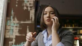 Droevige vrouw in comfortabele koffie die smartfone gebruiken stock video