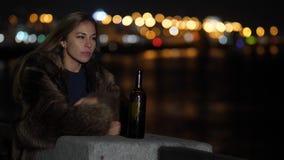 Droevige vrouw die alleen en gedeprimeerd bij nacht in stad het schreeuwen voelen Er is een fles wijn dichtbij haar Langzame Mo v stock footage