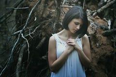 Droevige vrouw die in donker hout bidden royalty-vrije stock fotografie
