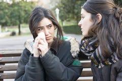 Droevige vrouw die en vriend het conforting in het park schreeuwen stock afbeelding