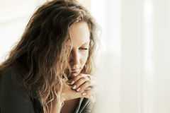 Droevige vrouw die met lange krullende haren neer kijken Royalty-vrije Stock Afbeelding