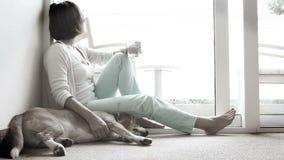 Droevige vrouw die op de vloer dichtbij de vriendschappelijke hond situeren stock video