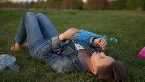 Droevige vrouw die op het gras onder plastic afval liggen die zijn gezicht behandelen met zijn handen Wanhoop van milieu stock video