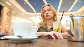 Droevige vrouw die op iemand in koffie en het drinken thee wachten slow-motion 4k, close-up, exemplaarruimte