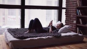 Droevige vrouw die smartphone gebruiken, liggend op bed door venster, die stadsstraat overzien stock video