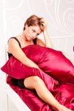 Droevige vrouw in een zwarte kleding op een bed stock afbeelding