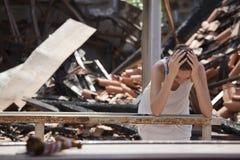 Droevige vrouw en vernietigd huis stock afbeeldingen