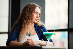 Droevige vrouw met cocktail. stock foto