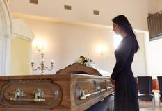 Droevige vrouw met doodskist bij begrafenis in kerk stock afbeelding