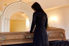 Droevige vrouw met doodskist bij begrafenis in kerk stock foto's