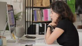 Droevige vrouw met een tatoegering op telefoon voor een computer op het werk stock video