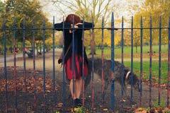 Droevige vrouw met hond in park Stock Afbeelding
