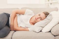 Droevige vrouw met maagpijn op laag thuis stock afbeelding