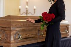 Droevige vrouw met rode rozen en doodskist bij begrafenis royalty-vrije stock afbeelding