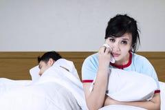 Droevige vrouw op een bed Stock Afbeeldingen