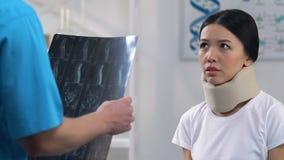 Droevige vrouw in schuim cervicale kraag bij artsenbenoeming, negatief x-ray resultaat stock video